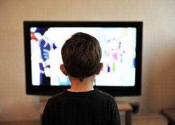 Niño sentado frente a televisor